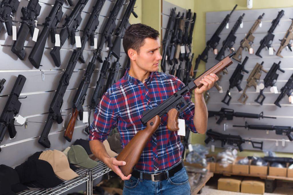 Male is choosing air-powered gun in army market.